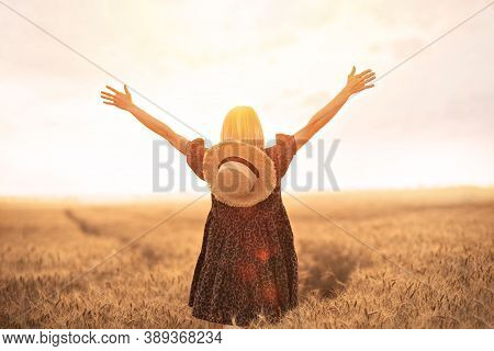 Backview Of Woman In Animal Print Dress, Straw Hat Holding Her Arms Up, Standing In Front Of Sun Wit
