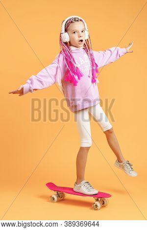 Active And Happy Girl With Curly Hair, Headphones Having Fun With Penny Board, Smiling Face Stand Sk
