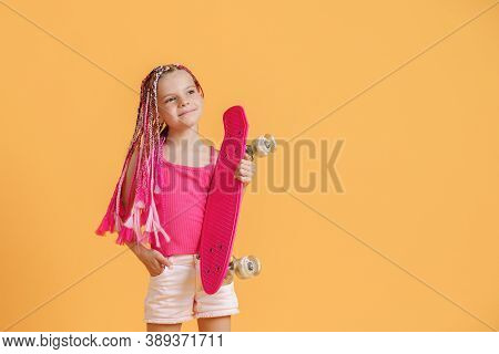 Active Young Girl With Dreadlocks In Pink Shirt And Shorts With Pennyboard Over Yellow Background.