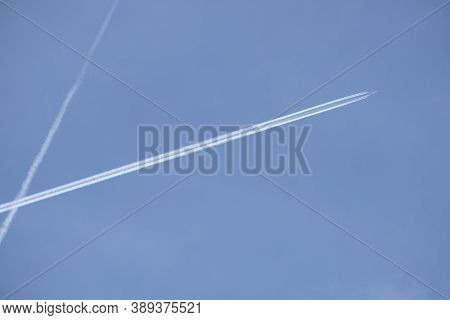 Long White Planes Traces Crossing In The Clear Cloudless Blue Sky And Big Passenger Supersonic Airpl