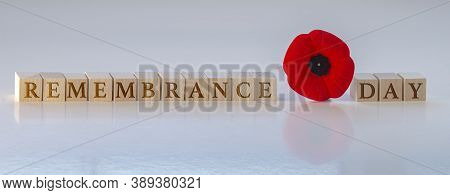 Remembrance Day, Text On Wood Blocks With A Poppy Flower. Concept: Remembrance Day.