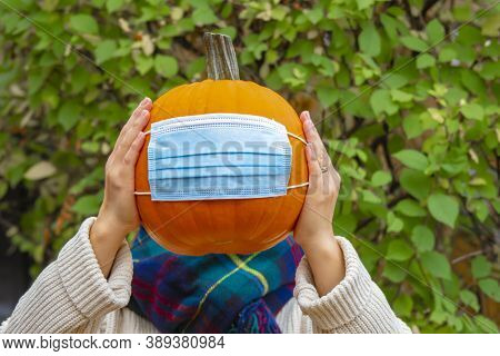 A Person Holding A Pumpkin Wearing A Facemask. Concept: Halloween And Thanksgiving During A Pandemic