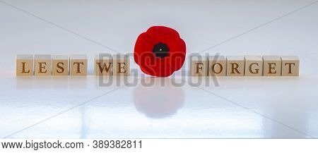 Lest We Forget, Text On Wood Blocks With A Poppy Flower. Concept: Remembrance Day.