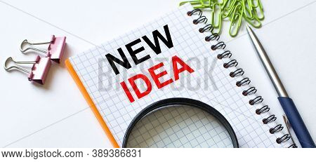 Notepad With Text New Idea On White Background With Clips, Pen And Magnifying Glass