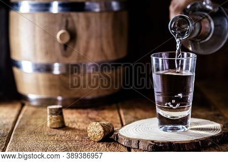 Glass Of Alcoholic Drink With Bottle, Hand Filling Glass. Image Of Bar, Pug, Spirits Of The Type Agu