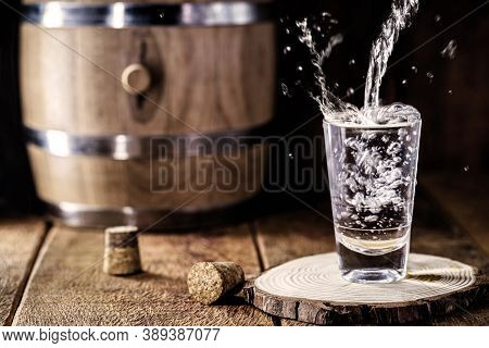 Pouring Distilled Alcohol Into A Shot Glass, Drops Flying, Served On Wooden Planks. Vintage Bench Wi