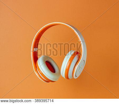 Orange Headphones On A Orange Background. Minimal Concept. Mock-up. Music. Levitation