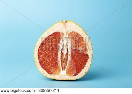 Grapefruit Minimal Erotic Concept. Half A Juicy Grapefruit Close Up On A Colored Background.