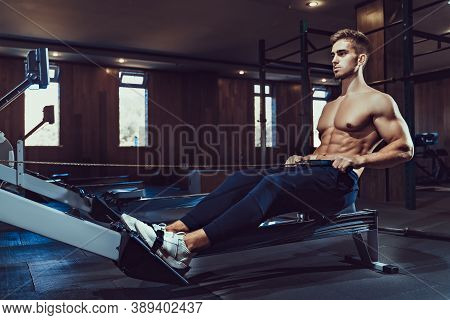 Muscular Bodybuilder In Sportswear Training Back Sitting On Exercise Machine. Side View Of Man With