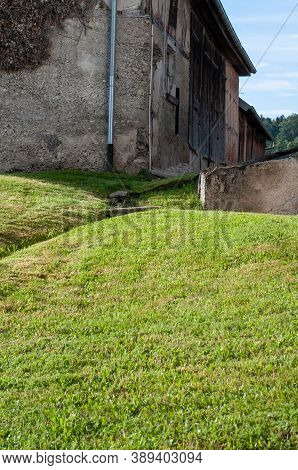 A Hilly Meadow On A Farmyard With An Old Weathered Barn In A Village In Germany
