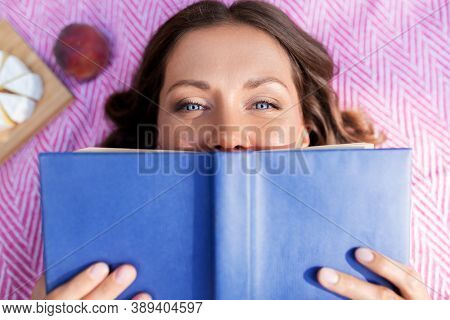 leisure and people concept - happy woman with picnic basket and food lying on blanket and reading book at summer park