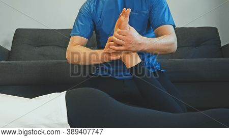 Therapist Massaging Woman's Leg At Her House. Medical Homecare.