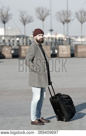 Man Bearded Hipster Travel With Big Luggage Bag On Wheels. Let Travel Begin. Traveler With Suitcase