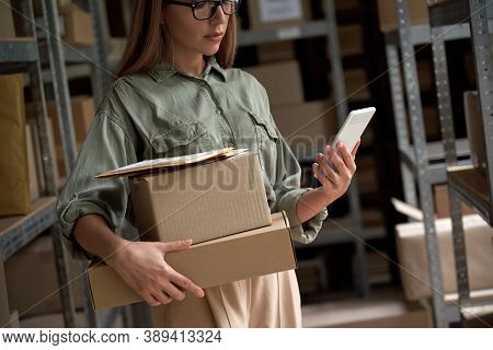 Female Warehouse Worker Manager, Small Stock Business Owner Holding Phone And Retail Package Parcel