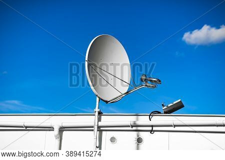 Sattelite Dish In The Blue Sky On The Roof Of The Industrial Building