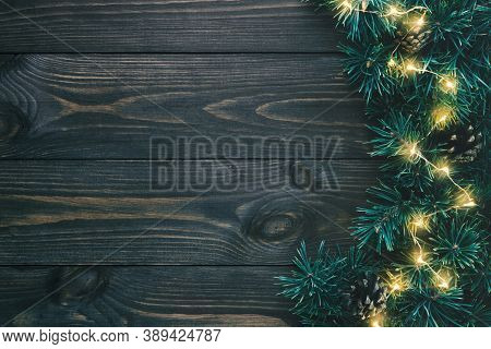 Fir Branches And Christmas Lights On Dark Wooden Background With Copy Space. Flat Lay, Top View.