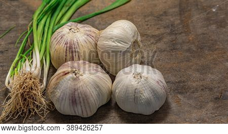 Garlic Bulb And Leaves On Old Wooden Background