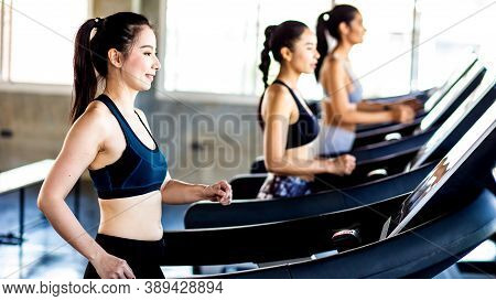 Attractive Asian Sport Women Running On Treadmil With Friend In Sport Gym