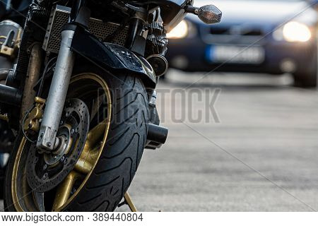 A Motorcycle Parked On The Sidewalk With A Blurred City Street With Cars In The Background, Selectiv