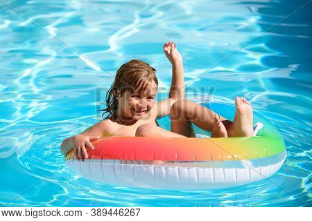 Children In Swimming Pool. Summer Outdoor. Happy Kid Playing With Colorful Swim Ring In Swimming Poo