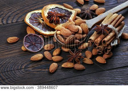 Almond Nuts In A Spoon And Dried Fruits On A Wooden Table Close Up. Almonds, Cinnamon, Anise Stars A