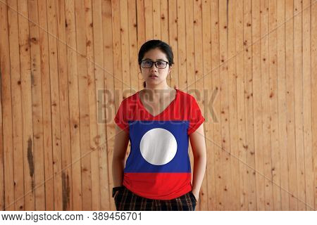 Woman Wearing Laos Flag Color Shirt And Standing With Two Hands In Pant Pockets On The Wooden Wall B