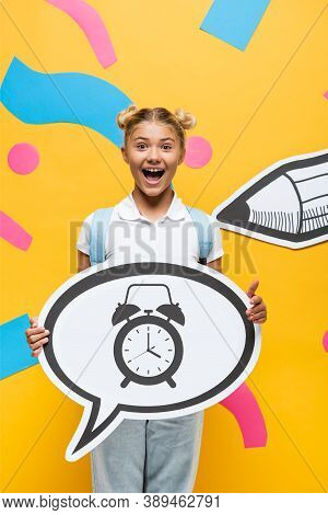 Schoolchild Holding Speech Bubble With Alarm Clock Illustration Near Paper Elements And Pencil On Ye