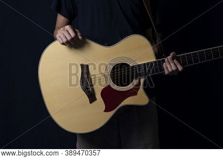 Musician At Night, Player With An Acoustic Guitar In The Dark, With Side Lighting.