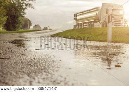 Truck Drives On A Wet Road In The Rain. Drives To Sunshine. Blurred Truck Due To Movement.