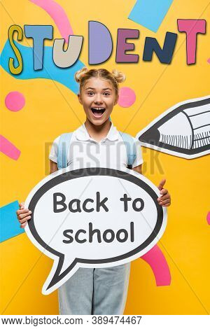 Schoolchild Holding Speech Bubble With Back To School Lettering Near Paper Elements And Pencil On Ye
