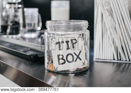 Glass Of Tip Box Tag And Few Coins Inside On Counter In Restaurant Or Cafe. Money Savings, Tips And