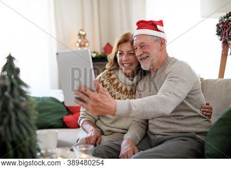 Side View Of Senior Couple Indoors At Home At Christmas, Having Video Call With Family.