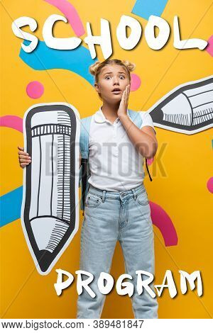 Schoolchild With Backpack And Paper Pencil Looking At Camera Near School Program Lettering On Yellow