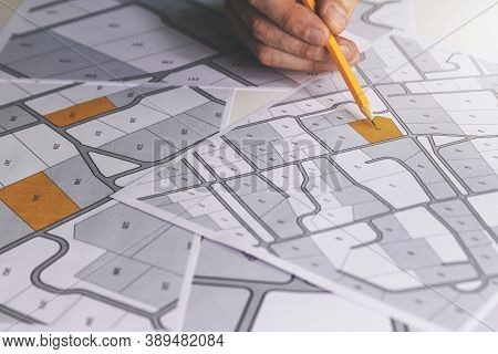 Hand With Pencil On Cadastral Map - Choose And Buy A Building Plot For House Construction