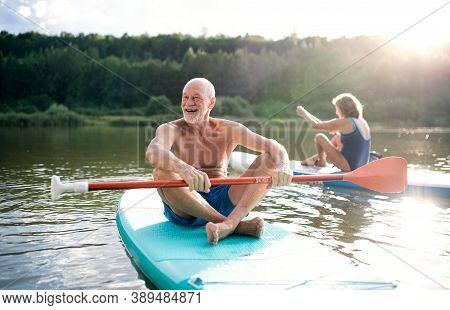 Senior Couple Paddleboarding On Lake In Summer.
