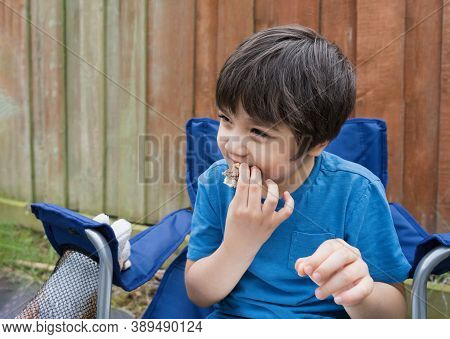 Kid Eating Burger Meat Ball In The Garden, Hungry Child Boy Siting Outside Eating His Homemade Picni