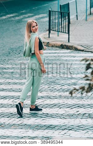 Stylish Beautiful Young Blond Woman In A Light Green Tracksuit Posing On The Street. Attractive Girl