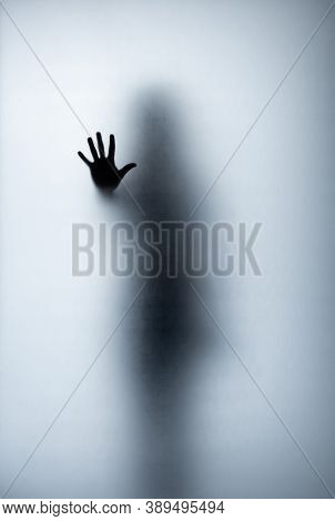 Horror Woman Silhouette In Window With Curtain. Horror Scene. Halloween Concept. Blurred Silhouette