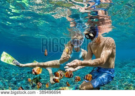 Happy Family Vacation. Young Couple In Snorkeling Mask Hold Hand, Dive Underwater With Fishes In Cor
