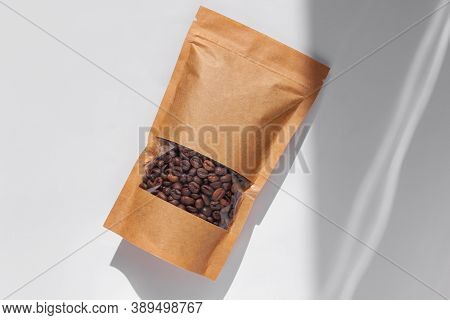 Brown Kraft Paper Pouch Bags With Coffee Beans Top View With Shadow Isolated On White Background.foo
