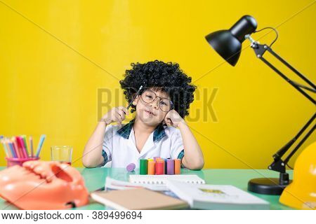 Boy Wearing A Wig Is Doing Homework, Questionable Expression At The Desk.