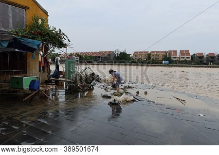 Hoi An, Vietnam, October 13, 2020: A Woman Cleans The Entrance Of Her Home Along The Thu Bon River A
