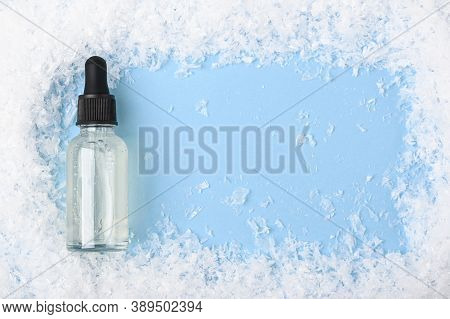 Serum In A Transparent Glass Bottle With A Pipette On A Blue Background With Snow. Moisturizing Skin