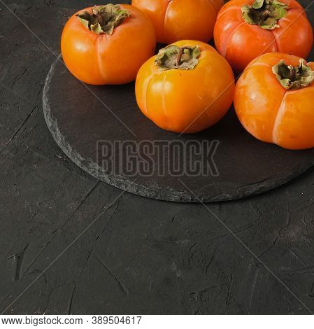 Group Of Fresh Orange Ripe Persimmon Fruits Laying On Round Black Slate On A Dark Background Texture