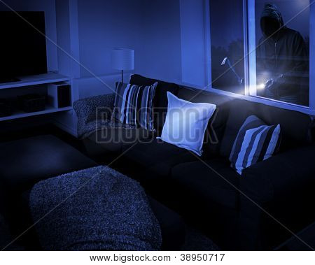 Unrecognizable person with flashlight and crowbar looking through living room window.