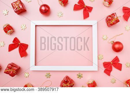 Christmas Greating Card Composition. Christmas Red And Golden Decorations With Frame On Pink Backgro