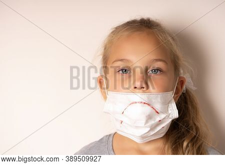 Sad Girl In A Medical Mask. She Painted A Sad Smile On The Mask.