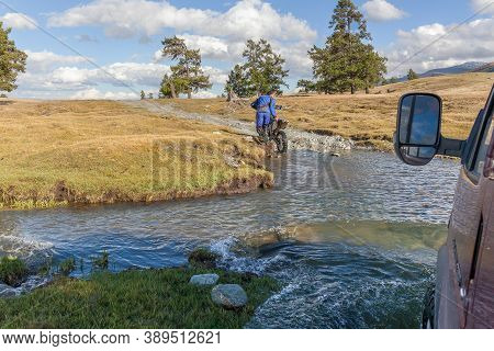 Altai, Mongolia - June 14, 2017: A Motorcyclist Pushes A Motorcycle Along A Road Flooded With Water.