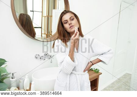 Woman With A Sponge Cotton Pad Problem Skin. A Picture Of A Happy Young Woman Cleaning Her Face With