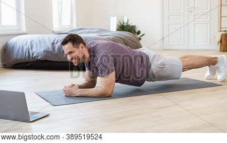 Fit Man Training At Laptop Doing Plank Exercise During Online Workout At Home. Guy Exercising On Flo